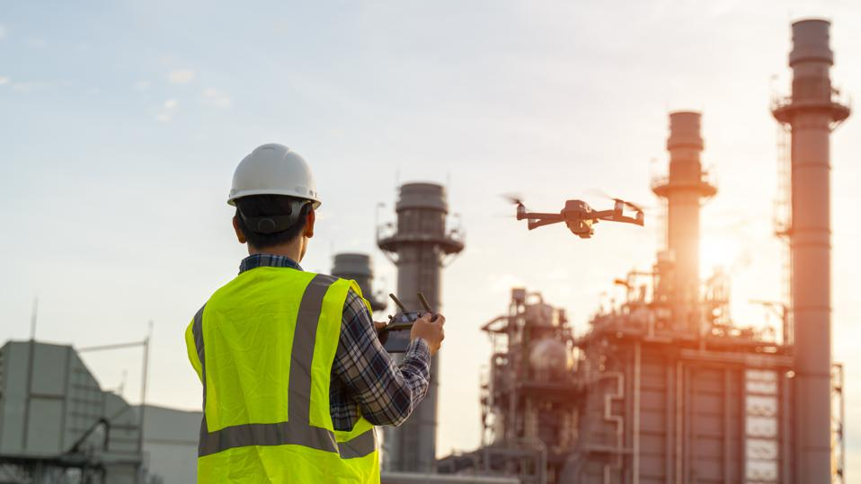 Construction worker piloting drone at a building site. Drones provide video surveillance or industrial inspection.