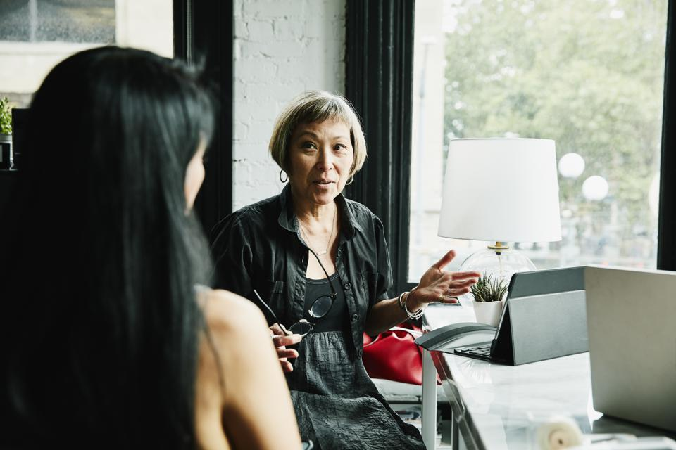 Mature businesswomen discussing project at desk in creative office
