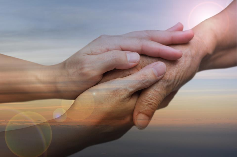 Caregiver, carer hand holding elder hand in hospice care with sky sunset background. Euthanasia  Philanthropy kindness to disabled concept.