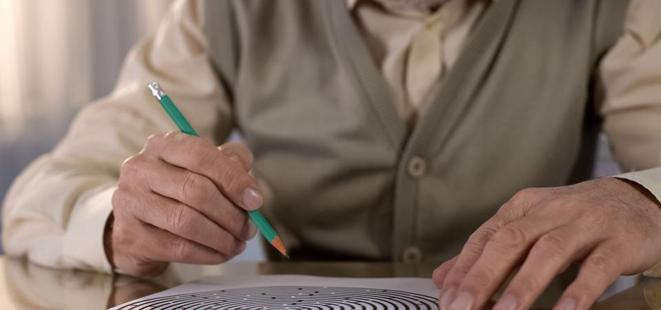 Concentrated retired man solving logic test at table, memory exercise, neurology