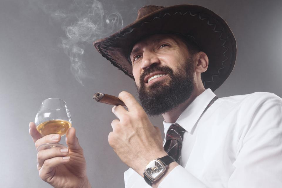 A bearded cowboy smoking a cigar and drinking