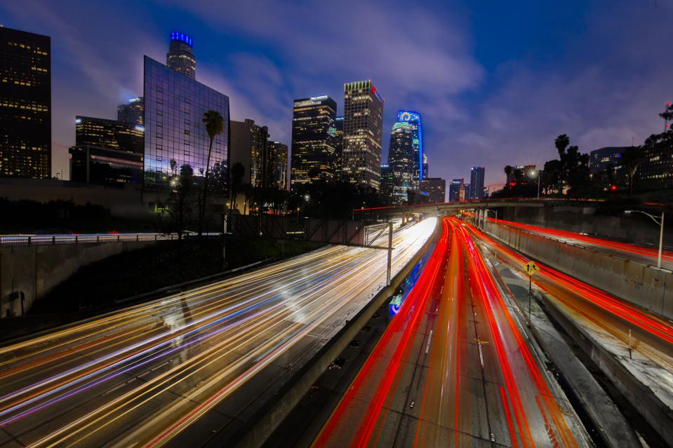 California 110 South leads to downtown Los Angeles with streaked car lights at sunset