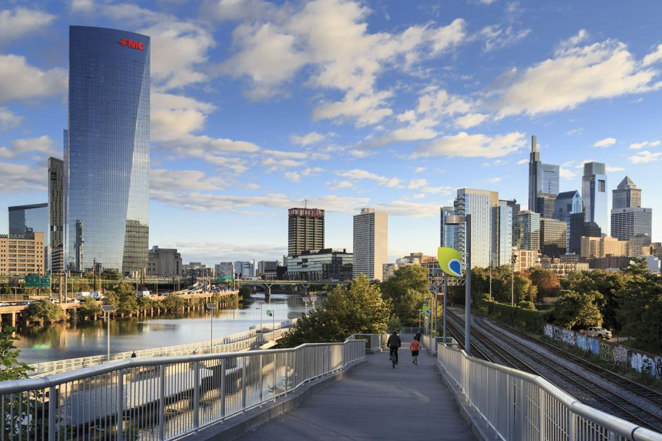 Philadelphia Skyline with Schuylkill River Park Boardwalk in Autumn with Bikers and Joggers, Philadelphia, Pennsylvania, USA