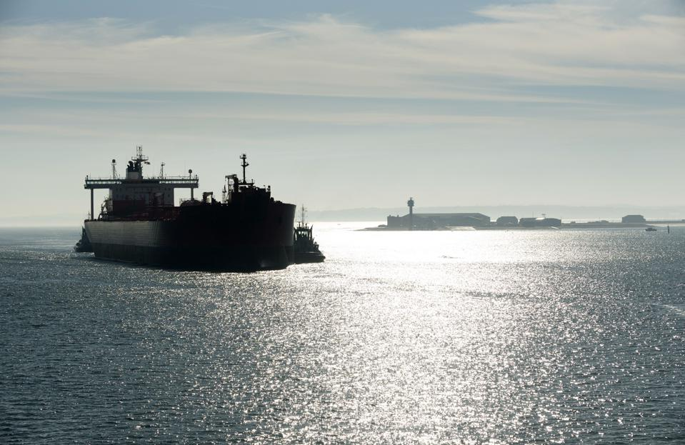 Southampton Water, Hampshire, England, UK, Early morning against the light shot of a tug in attendance moving a broad beam oil tanker onto a berth at Fawley refinery