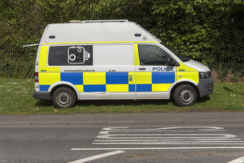 Police van and camera checking for speeding motorists parked on a grass verge in Kings Worthy