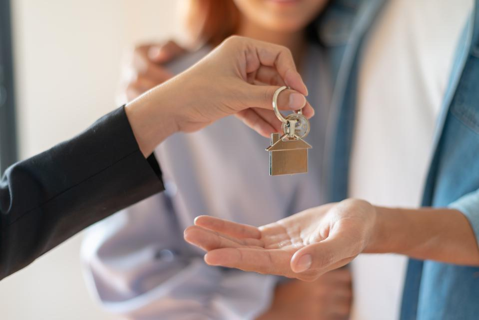 Young Asian couple receiving new apartment or room key from realtor or real estate sales agent after finish a rental or buying contract.