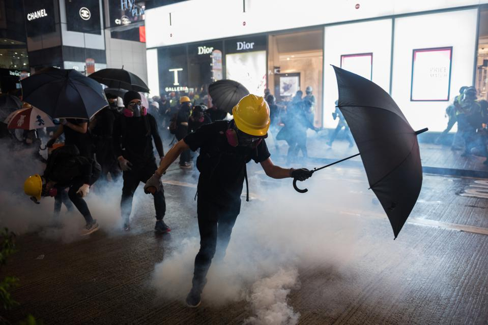 A protester attempts to kick back a tear gas round fired by...