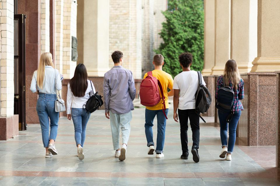 Group of students walking in college campus after classes