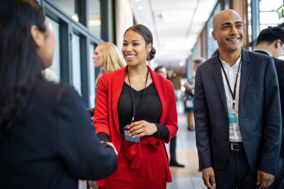 Business people greeting each other in coffee break at seminar