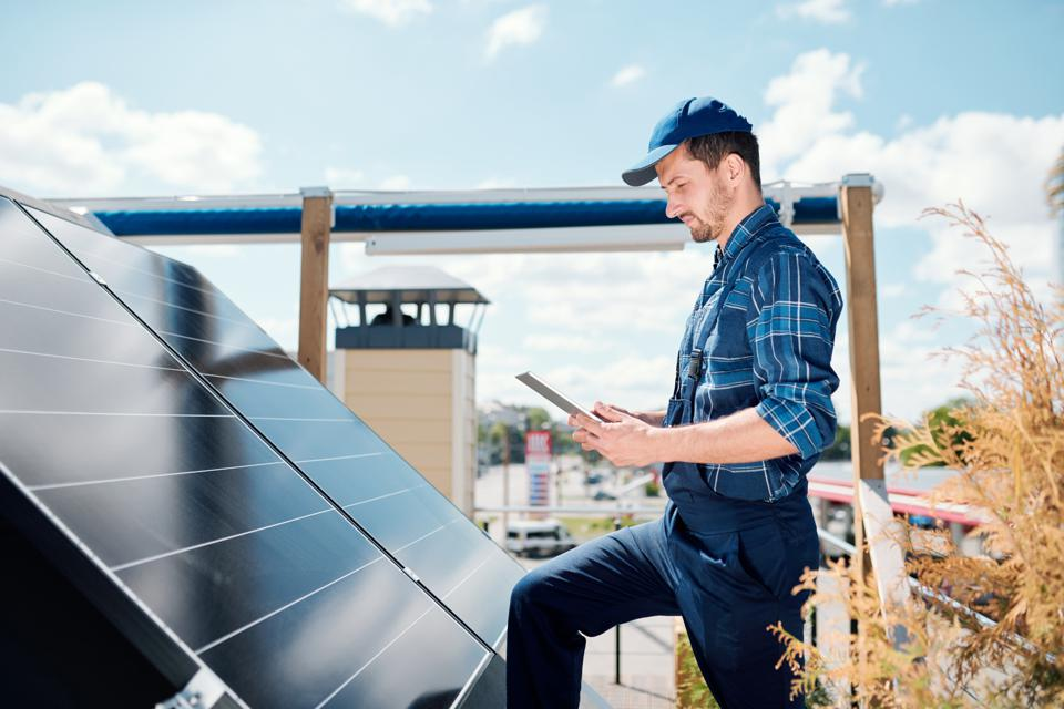 Man with tablet searching for online data about solar panels