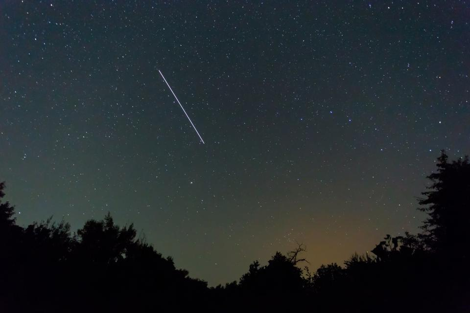 night starry sky with iss track above the forest silhouette