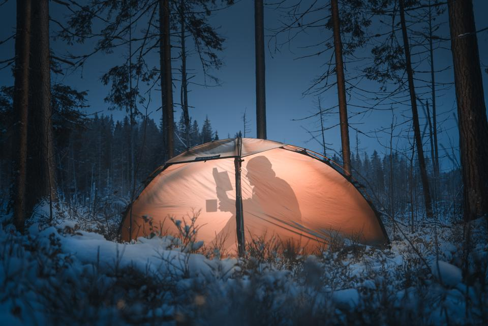 Shadow Of Man Reading Book In Illuminated Tent At Snow Covered Forest During Night