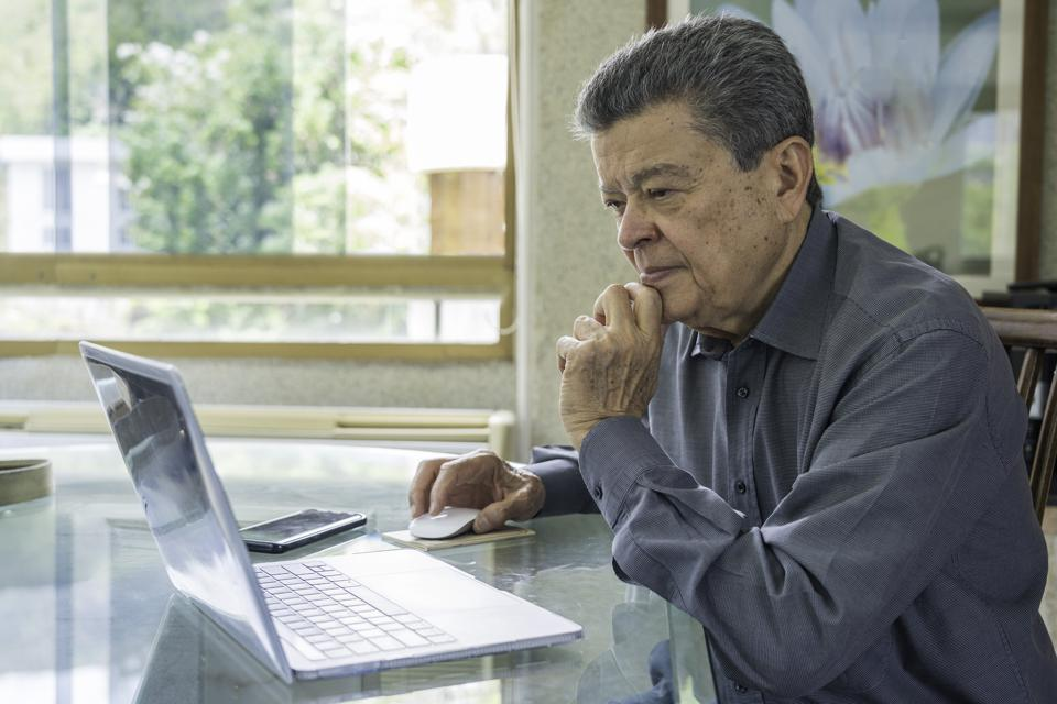 Hispanic senior man working at home office with laptop computer. Home office concepts.