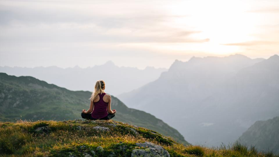 Woman performs yoga moves on mountain summit