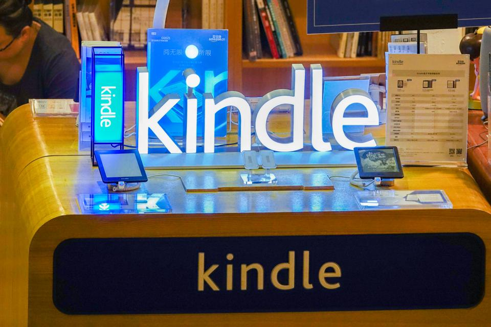 a Kindle sign on a table with Kindle e-readers in a bookstore
