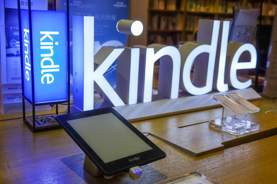 an e-reader sitting on a table with a Kindle sign behind it