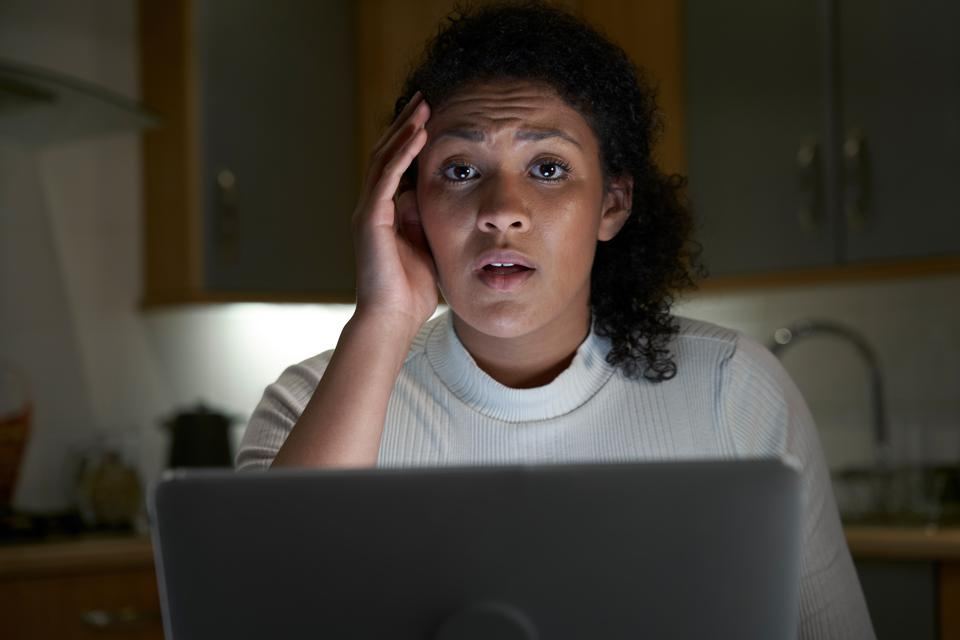 Portrait Of Unhappy Woman At Home With Computer Victim Of Online Crime