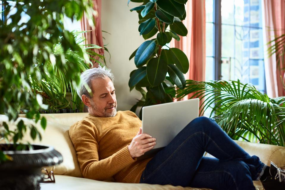 Mature man using laptop on sofa at home