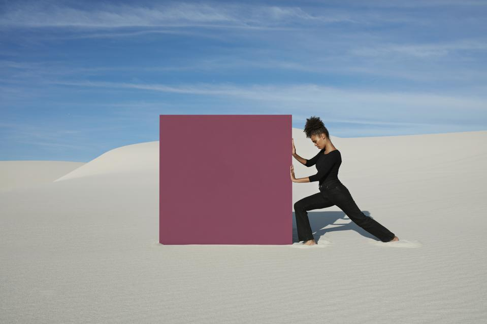 Young woman pushing maroon portal on white sand dunes at desert