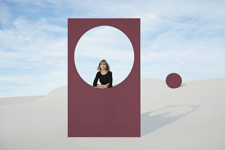 Portrait of young woman standing by maroon portal at desert