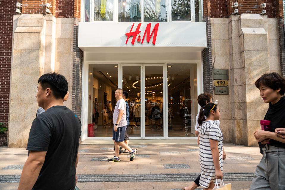 Pedestrians walk past an H&M store in Shanghai.