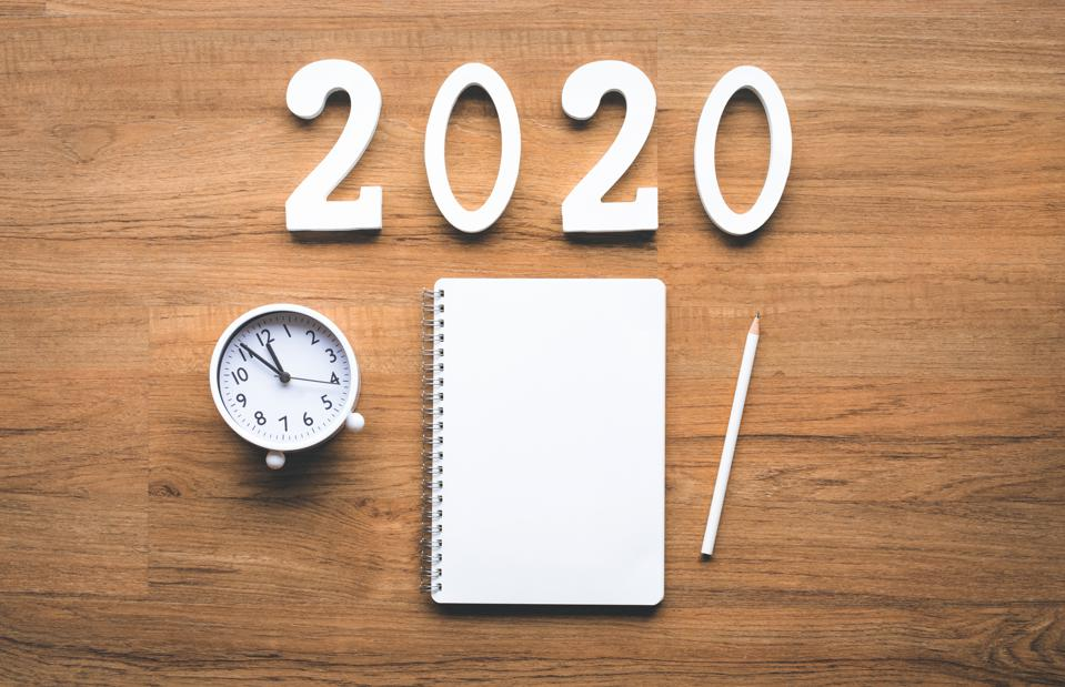 Celebration and countdown of new year 2020 concepts with text number and alarm clock and notepaper on wood background