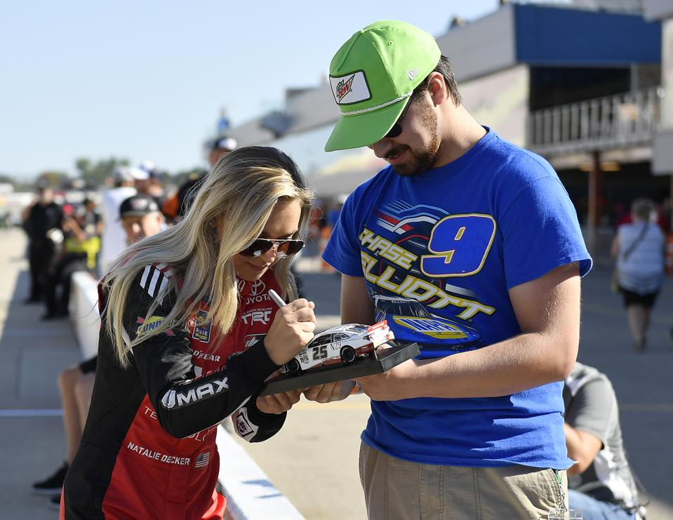 Decker signs an autograph for a Chase Elliott super fan, at Michigan Intl Speedway