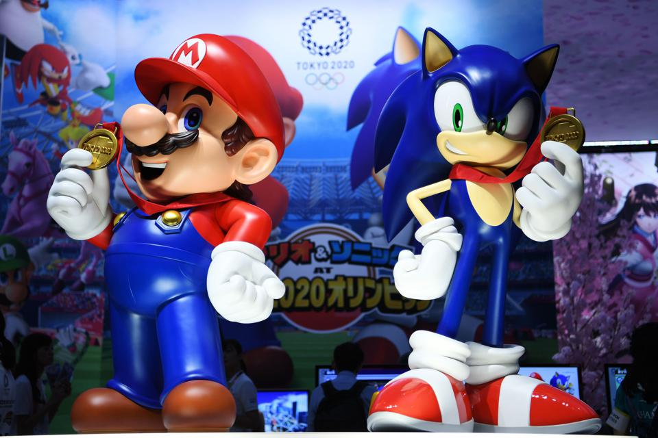 Mario and Sonic from Nintendo games holding gold medals with Tokyo 2020 Olympics banner behind
