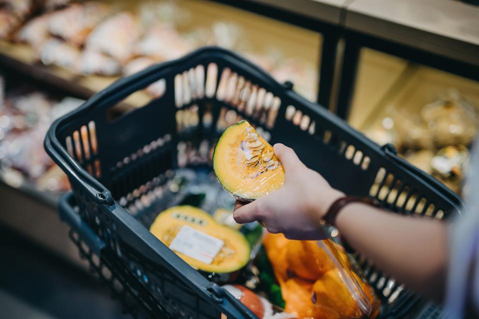 Close up of woman's hand putting fresh produce into shopping cart while grocery shopping in supermarket