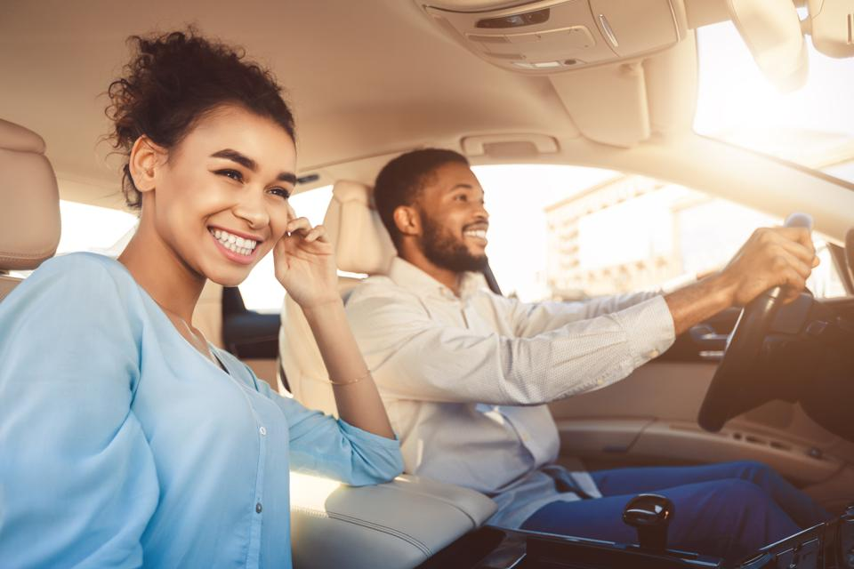 Young african american couple driving in car, travelling together