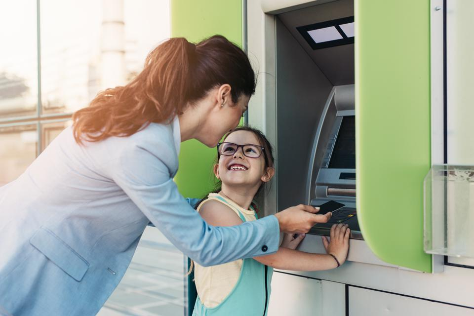Mother and daughter using ATM machine