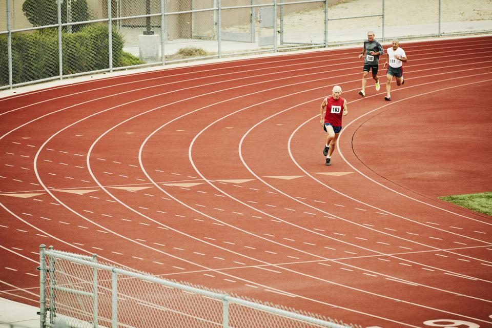 Senior male track athletes running distance race on track