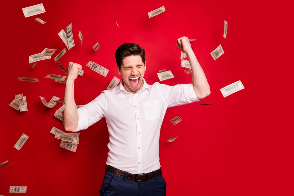 Photo of ecstatic overjoyed man rained with bucks banknotes achieving success while isolated with red background