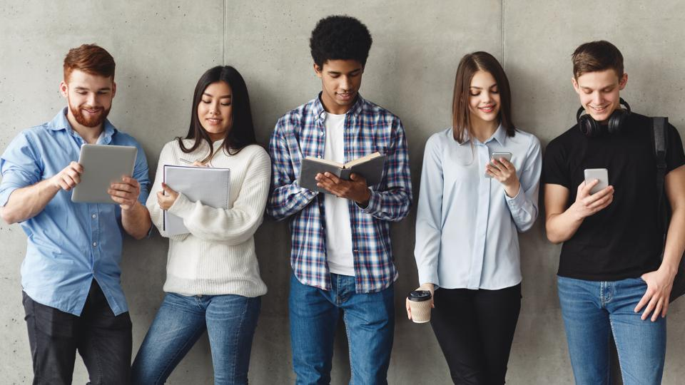 Diverse students with books standing near grey wall