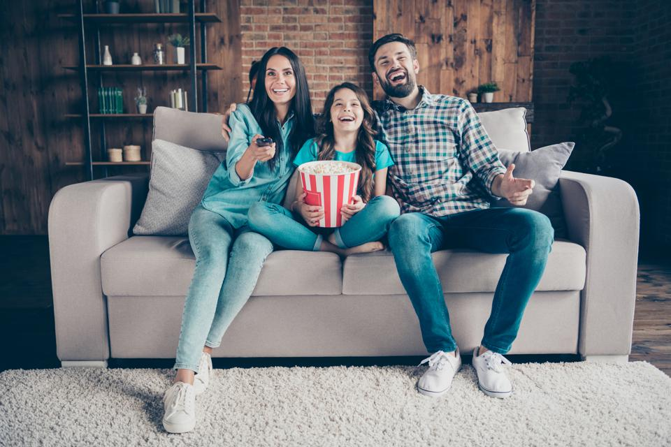 Portrait of cheerful mom dad and little kid have rest laugh look funny film wear denim jeans checkered shirt t-shirt sit divan in house indoors
