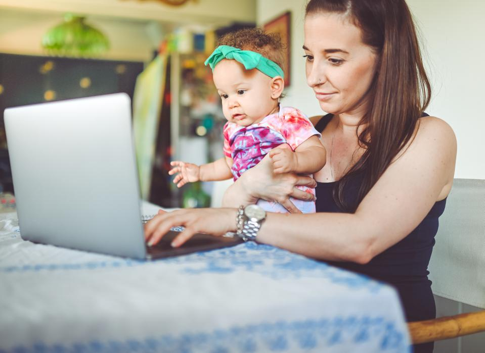 Mother and baby sit in front of a laptop for telemedicine
