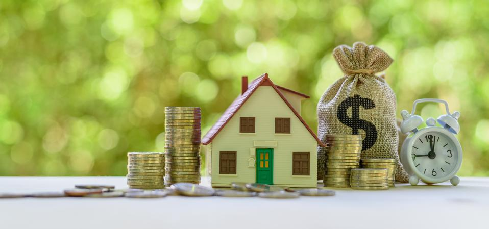 Managing your mortgage loan : house model, coins, US dollar bag, white clock on a table.
