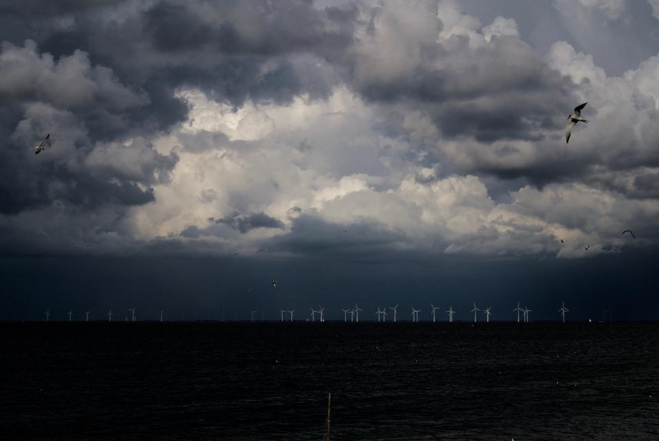 Threatening sky on a dark sea with on the horizon wind turbines off the Netherlands.