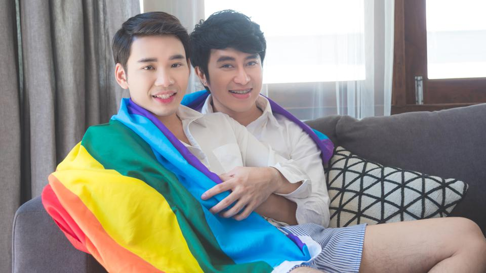 Portrait Of Gay Couple Holding Rainbow Flag While Relaxing On Sofa At Home Pride Month: 500 Prides Cancel Amid Coronavirus So Here Is A List Of LGBT Digital Pride Events