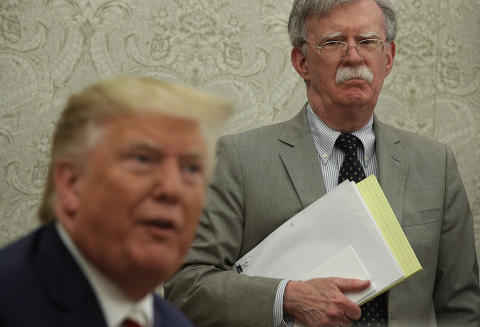 President Trump speaks to members of the media as National Security Adviser John Bolton listens in the Oval Office in August 2019.
