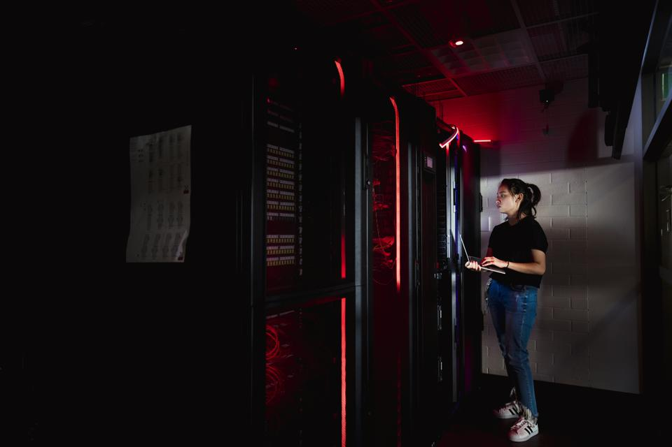 Female Technician Working in Server Room