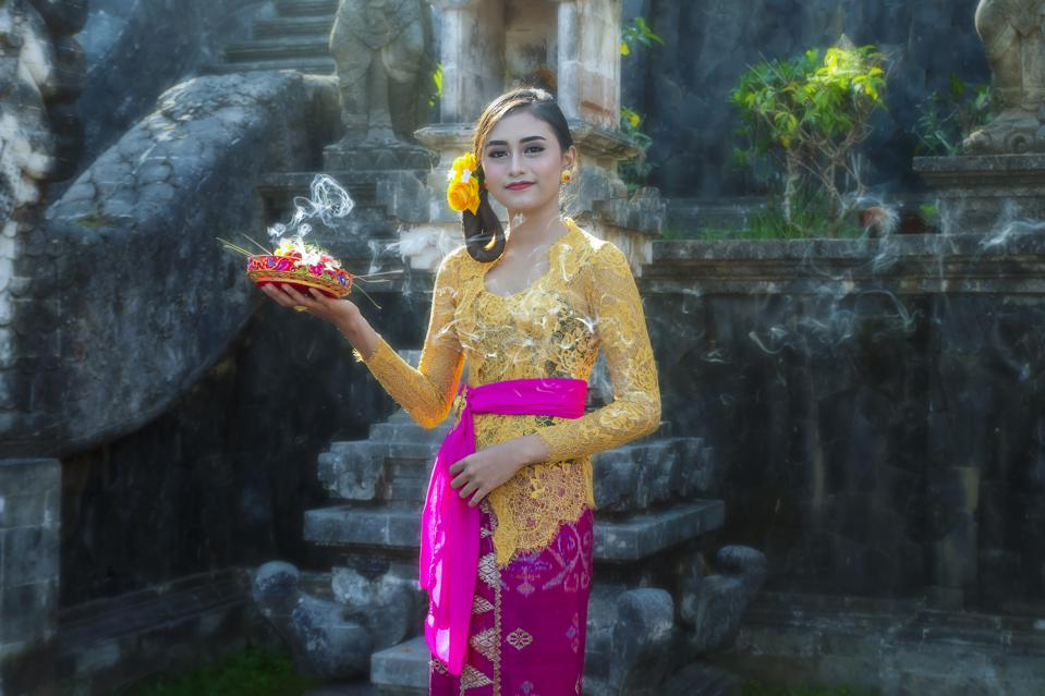 Balinese woman wearing traditional costume with accessories,offering,ornaments in hinduist temple in bali Indonesia