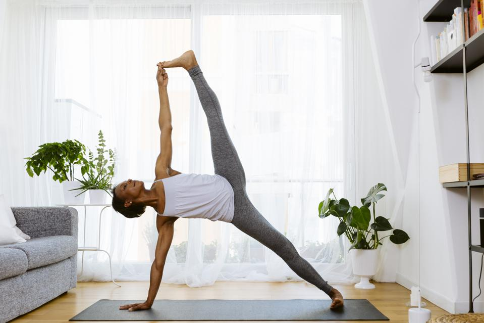 Woman practicing yoga at home, side plank holding one leg in air