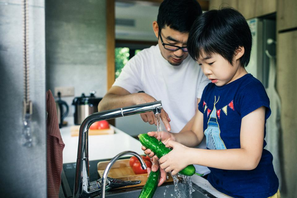 Father and son washing Fresh fruit in kitchen sink