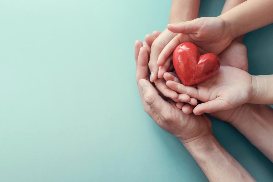 adult and child hands holding red heart on aqua background, heart health, donation, CSR concept, world heart day, world health day, family day