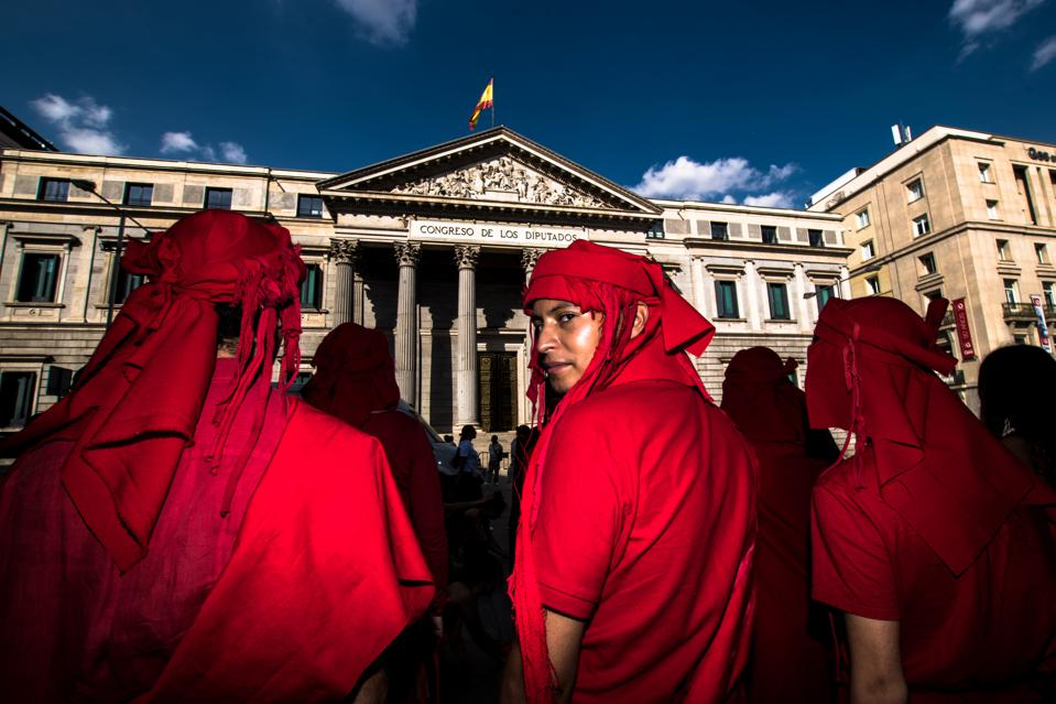 Extinction Rebellion activists wearing red outfits gather in...
