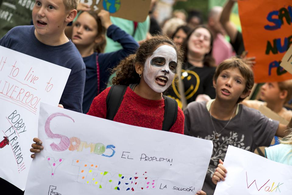 Children hold placards while chanting slogans during the...