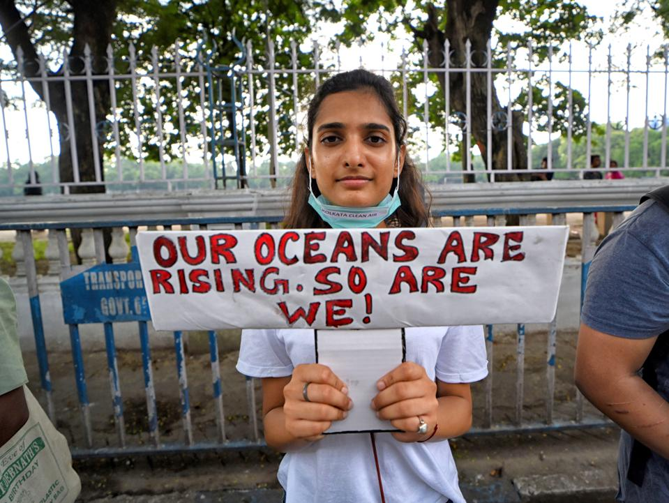 A student holds a placard that says our oceans are rising so...