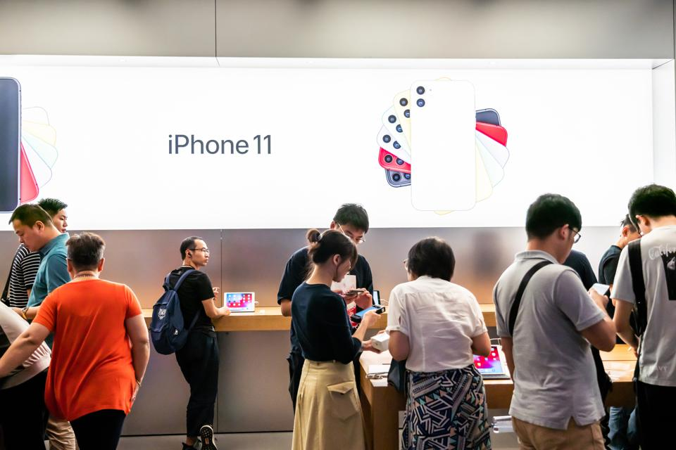 Customers look at the Apple's new iPhone 11 series...