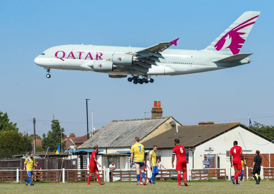 A Qatar Airways plane comes in to land at London's Heathrow Airport, passing the Cherry Red Records Combined Counties Football League Division One match between Bedfont & Feltham and AFC Hayes on August 26, 2019 in Bedfont, England.